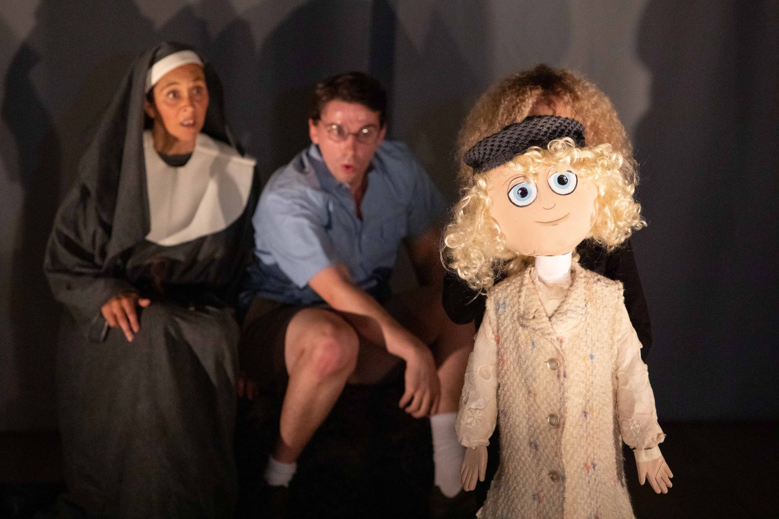 A puppet of a little girl looks ahead while behind a quizical nun and schoolboy look on.